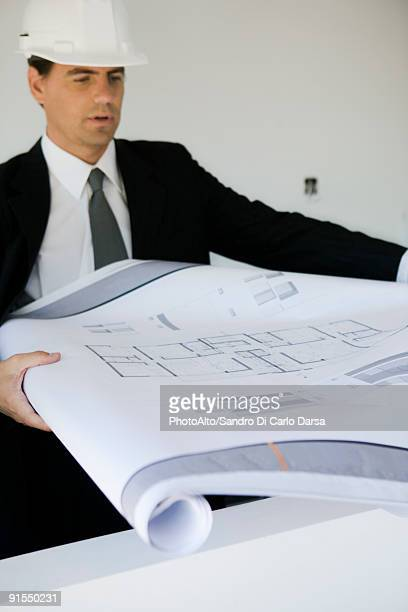 Man in suit and hard hat unrolling blueprint