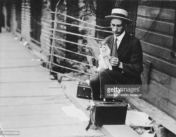 Man in suit and hat seated against a fence holding a cat with two small black cases at his feet. From a photograph album of images taken by...