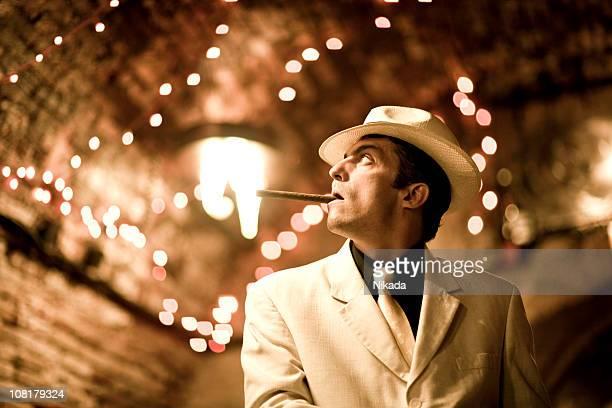 Homme en costume et chapeau fumeurs de cigare