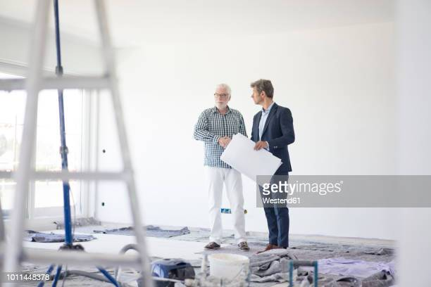 Man in suit and senior man talking on room under construction