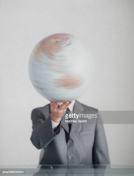 Man in suit at table holding globe with one hand in front of head