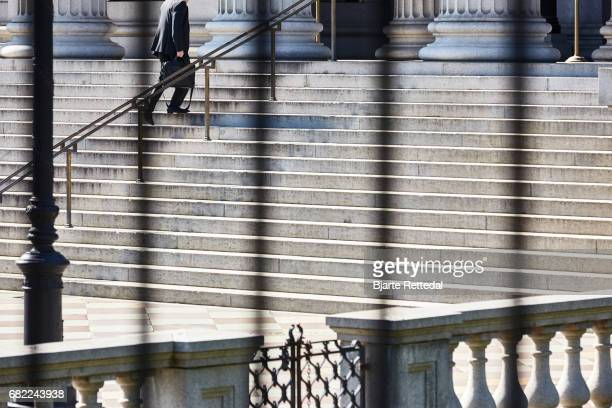 Man in suit climbing the stairs to the Treasury Department in Washington DC