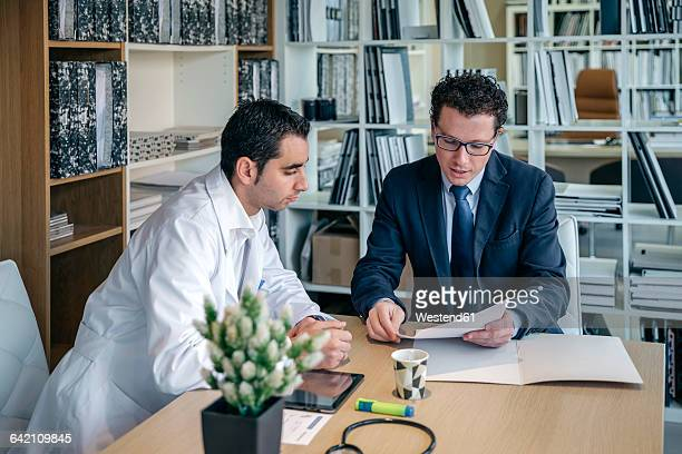 Man in suit explaining documents to doctor in medical office