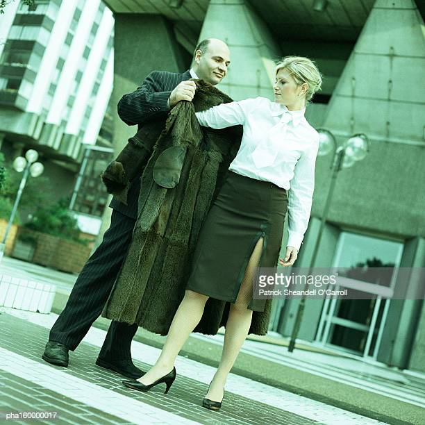 Man in suit helping woman on with coat.
