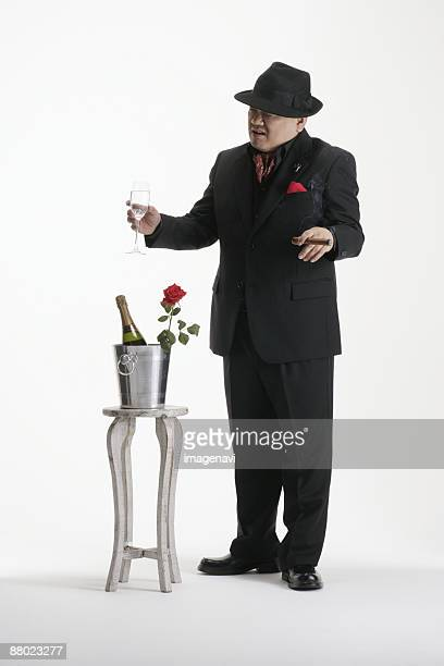A man in suit holding a glass