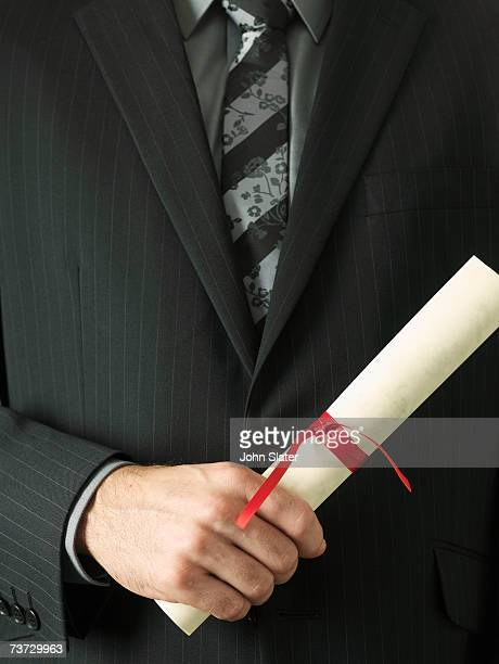 'Man in suit holding diploma, mid section'