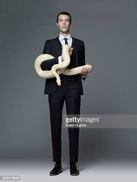 Man in suit holding snake