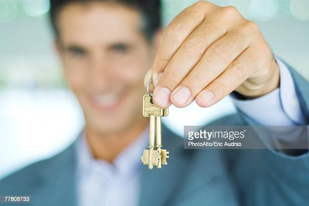 Man in suit holding up keys, focus on hand holding keys in foreground