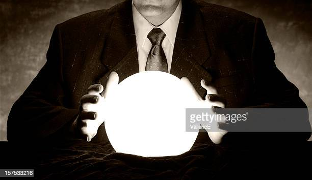 man in suit holds hands over glowing crystal ball - calculating stock pictures, royalty-free photos & images