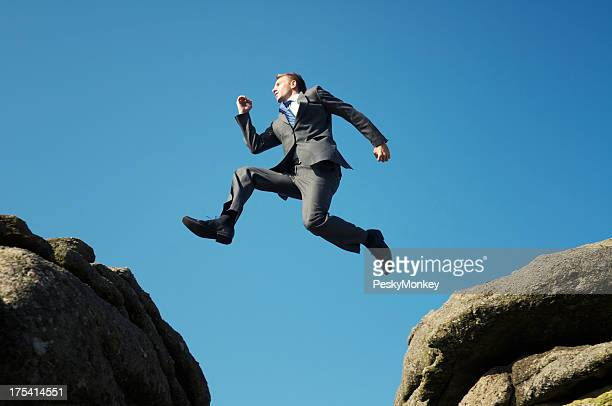 Man in suit jumping between towering rocks