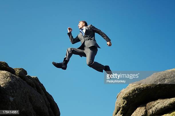 Mann in Anzug springen zwischen hohen Felsen