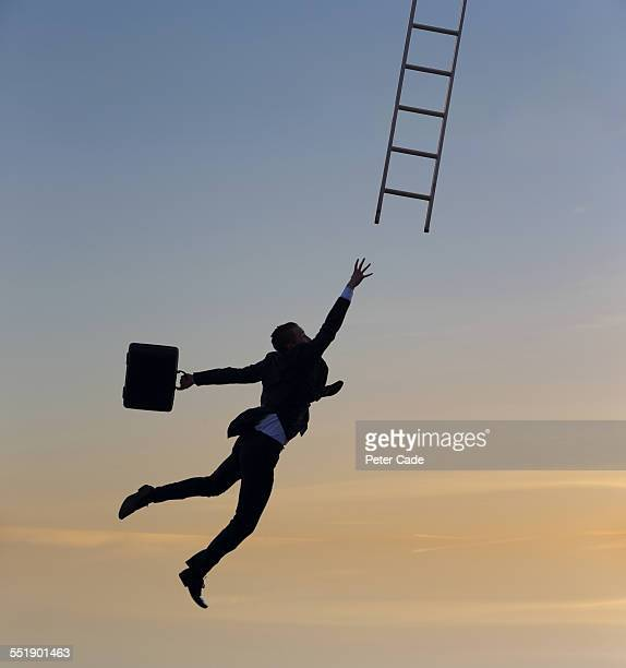 man in suit jumping for ladder, sunset, silhouette