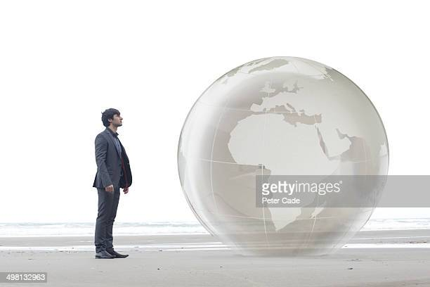 Man in suit looking at giant globe on beach