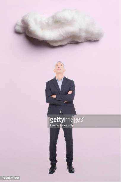 Man in suit looking up at a cloud