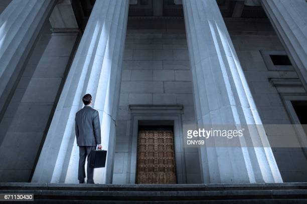 Man In Suit Looking Up At Courthouse