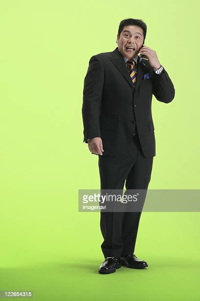 a man in suit making a call on his cellphone - metabolic syndrome stock pictures, royalty-free photos & images