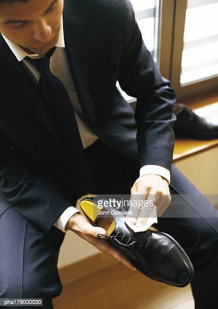 Man in suit polishing shoe, close-up