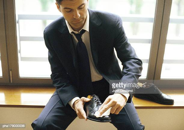 Man in suit polishing shoe, close-up