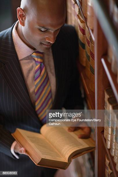man in suit reading book in library