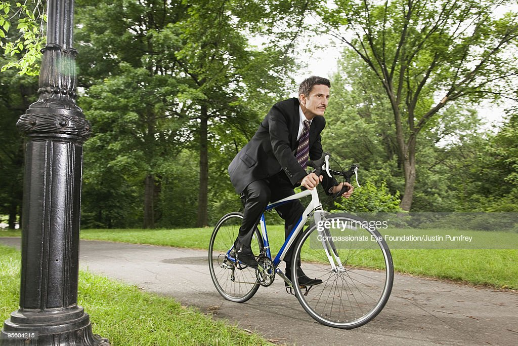 man in suit riding a pedal bike : Stock Photo