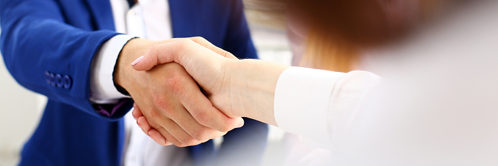 Man in suit shake hand as hello in office closeup 1070900014