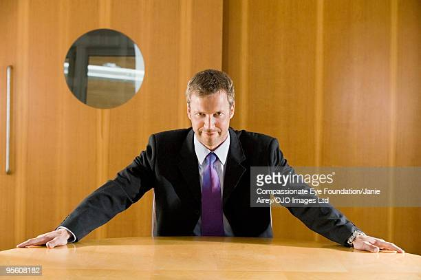 """man in suit sitting with arms on table - """"compassionate eye"""" stock pictures, royalty-free photos & images"""