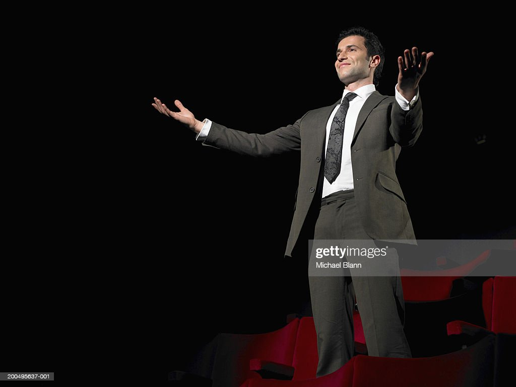 Man in suit standing in dark cinema with arms out : Stock Photo