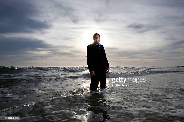 man in suit standing in ocean