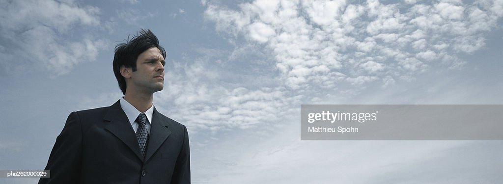 Man in suit standing with sky in background, low angle view : Stockfoto