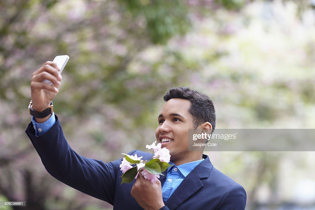 Man in suit taking cell phone selfie while holding flowers : Stock Photo