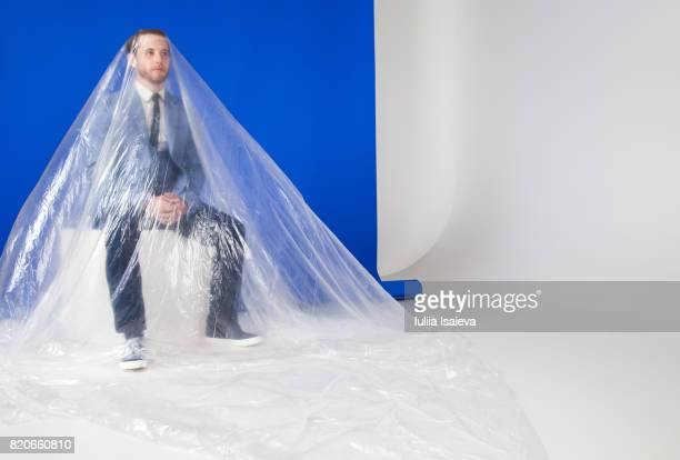 man in suit under plastic - man wrapped in plastic stock pictures, royalty-free photos & images