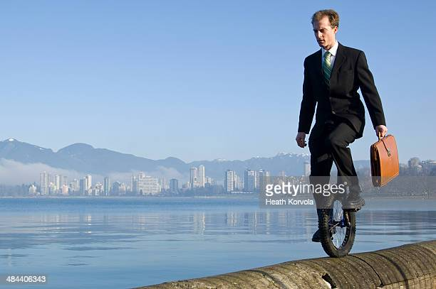 Man in suit unicycles with city in background.