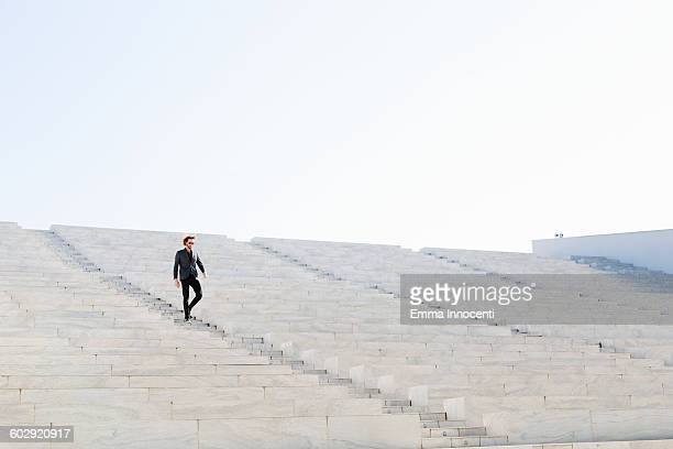 Man in suit walking down white staircase