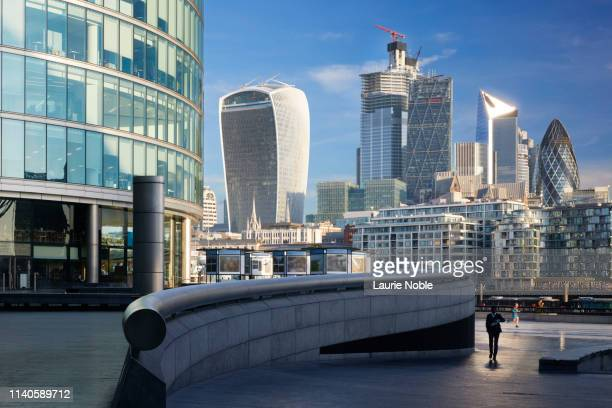 man in suit walking in front of london skyline, london,uk - architecture stock pictures, royalty-free photos & images