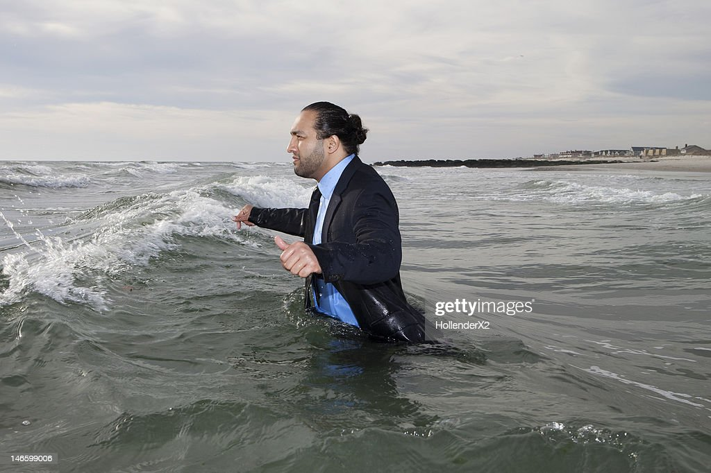 man in suit walking into ocean : Stock Photo