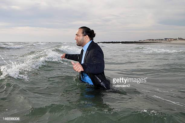 man in suit walking into ocean - waist deep in water stock pictures, royalty-free photos & images