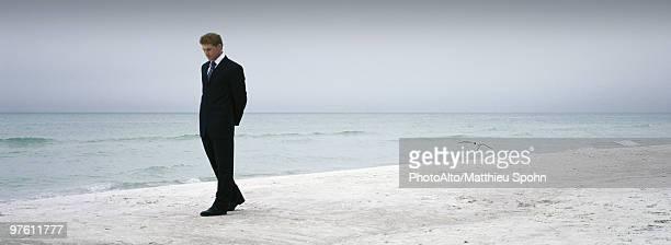 man in suit walking on beach - 後ろ手 ストックフォトと画像