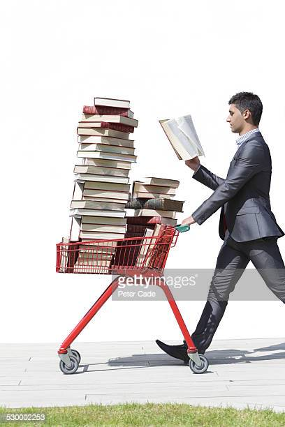 man in suit walking with books in trolley