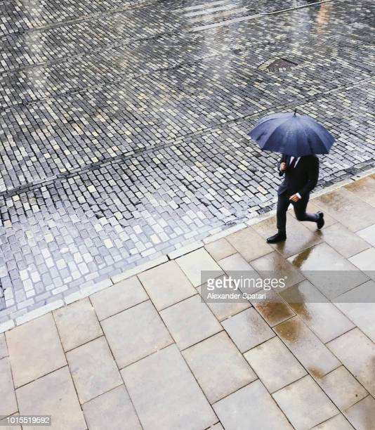 Man in suit walking with umbrella under rain on a cobbled street, high angle view