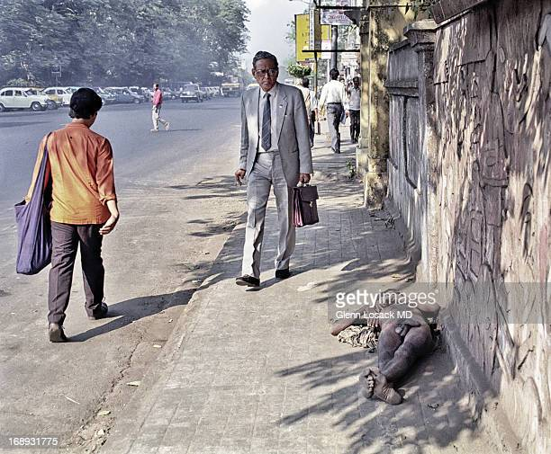 CONTENT] man in suit walks down the streets of Kolkata peers at homeless man laying nude on the sidewalk as as another man walks by Kolkata India