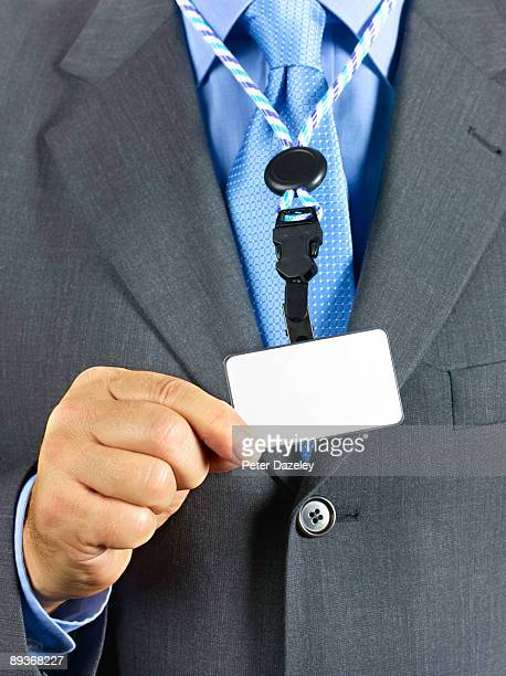 Man in suit wearing blank security ID badge.