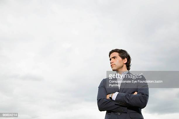 "man in suit with arms crossed - ""compassionate eye"" stock-fotos und bilder"