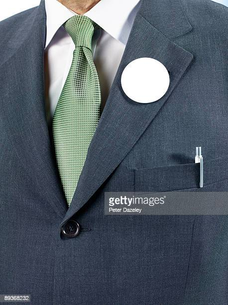 Man in suit with blank button badge.