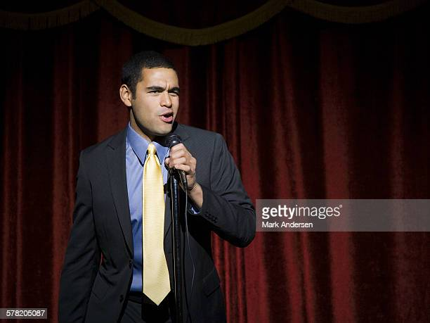 Man in suit with microphone making funny faces