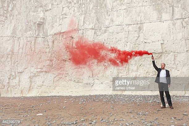man in suit with red flare on chalk cliff