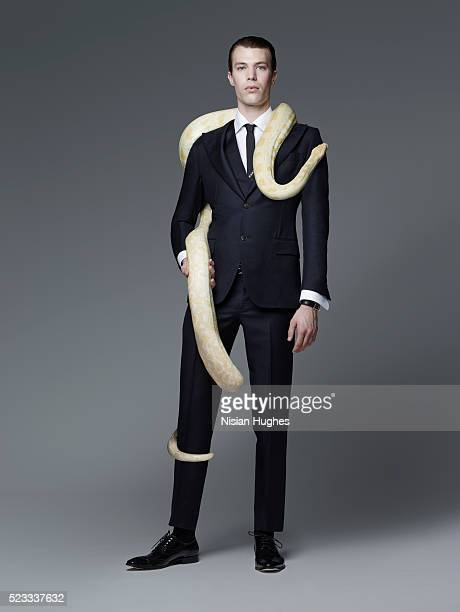 Man in suit with snake wrapped around him