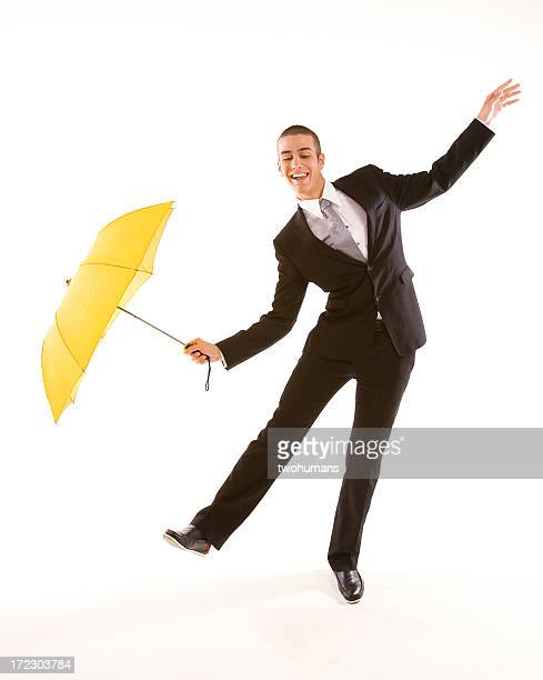 Man in suit with yellow umbrella doing funny business