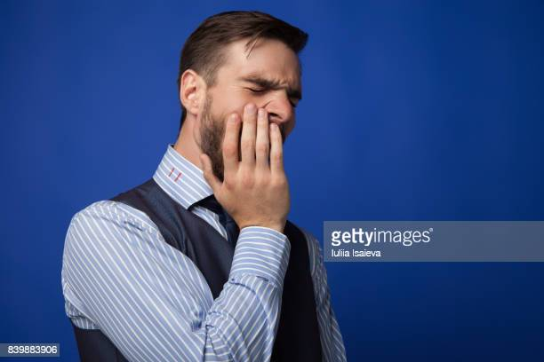 Man in suit yawning on blue