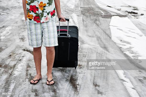 Man in summerwear with suitcase in snow