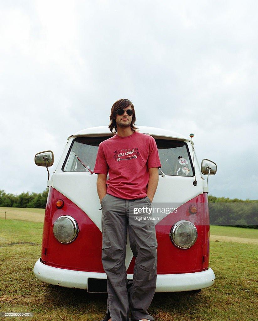 Man in sunglasses standing in front of camper van, hands in pockets : Stock Photo